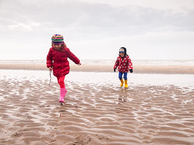 small boy and girl in winter clothing and rubber boots spalshing in a tidal pool on a winter beach