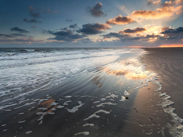 dramatic sunrise over North sea beach, Netherlands